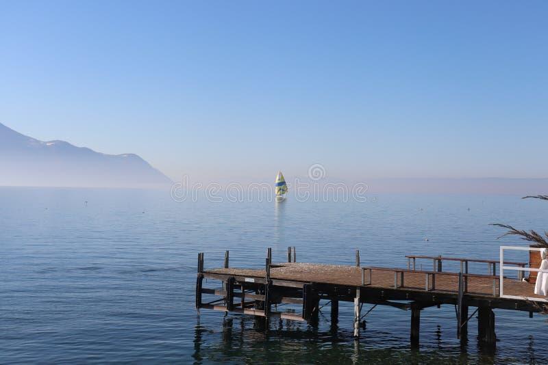 Peque?o muelle de madera que estira adentro al lago con el cielo azul, el abofe de la niebla el lago y la silueta de la monta?a e fotografía de archivo