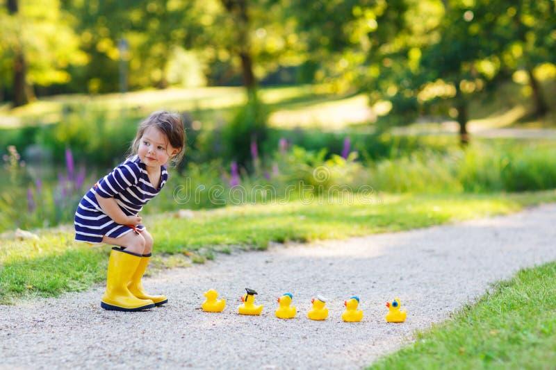 Pequeño niño adorable de 2 que juegan con los patos de goma amarillos en s foto de archivo libre de regalías