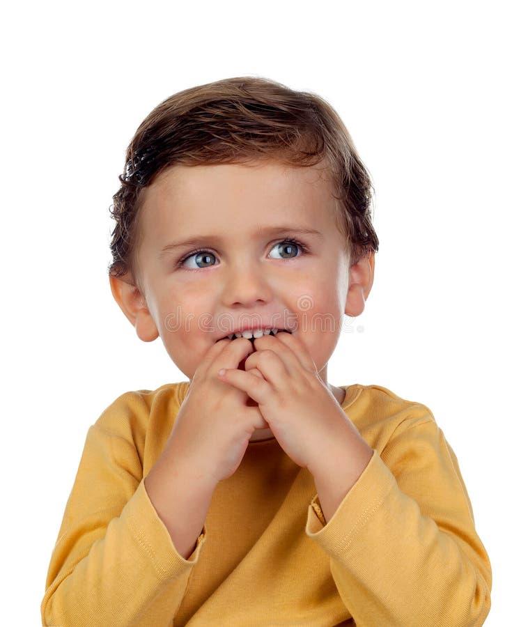 Pequeño niño adorable dos años que chupan su mano aislada encendido foto de archivo