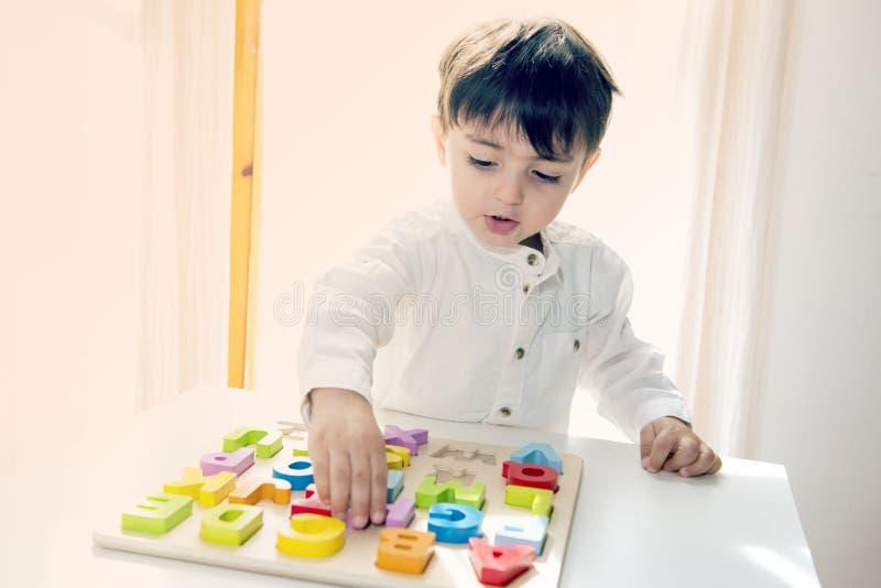 Pequeño niño adorable que juega con las letras de madera coloridas fotos de archivo