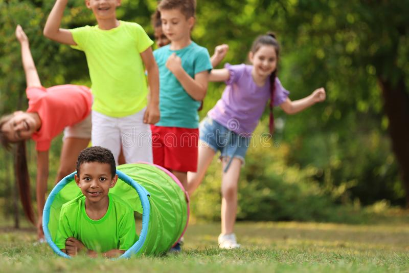 Pequeño niño afroamericano lindo que juega con los amigos en parque imagen de archivo libre de regalías