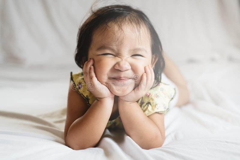 Pequeño niño asiático lindo de la muchacha que sonríe en cama fotografía de archivo