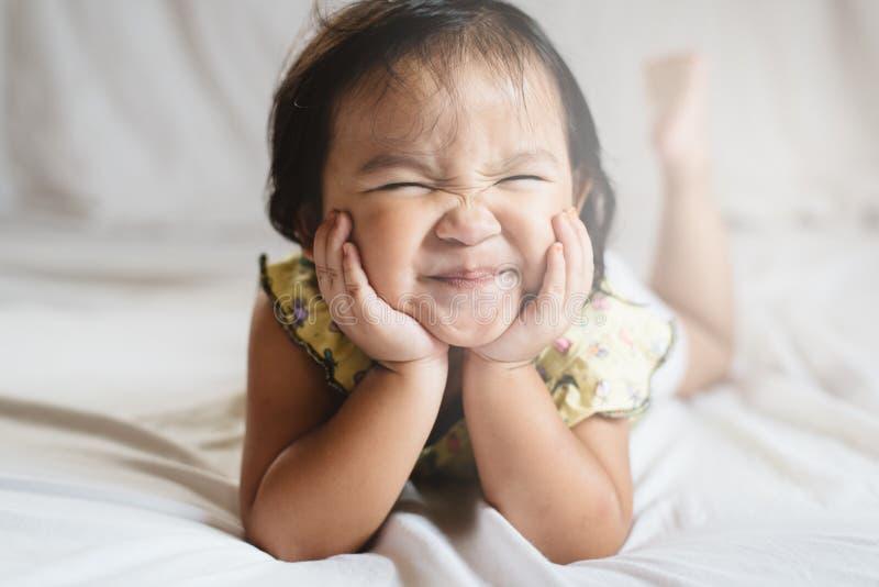 Pequeño niño asiático lindo de la muchacha que sonríe en cama imagen de archivo