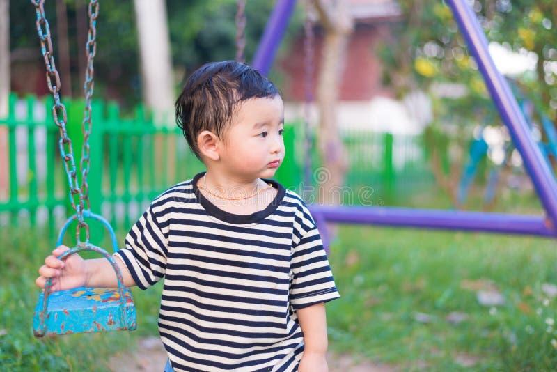 Pequeño niño asiático triste en el patio bajo luz del sol en suma foto de archivo