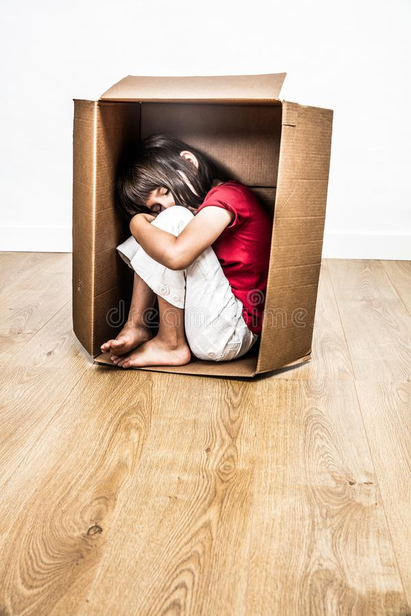 Pequeño niño cansado durmiente solo hunched en una caja de cartón imágenes de archivo libres de regalías