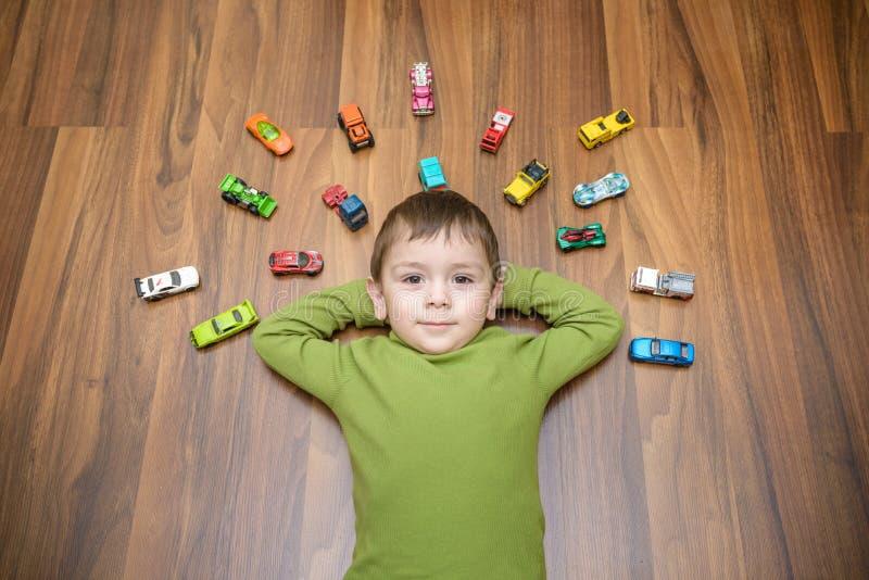 Pequeño niño caucásico que juega con las porciones de coches del juguete interiores Muchacho del niño que lleva la camisa verde P foto de archivo