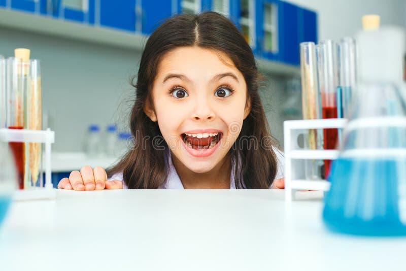 Pequeño niño con el aprendizaje de la clase en grimase del laboratorio de la escuela fotos de archivo libres de regalías