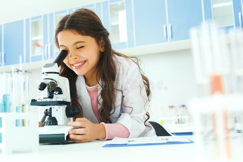 Pequeño niño con el aprendizaje de la clase en laboratorio de la escuela usando el microscopio fotografía de archivo