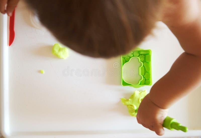 Pequeño niño contratado al playdough que modela en la tabla, visión superior lifestyle foto de archivo libre de regalías