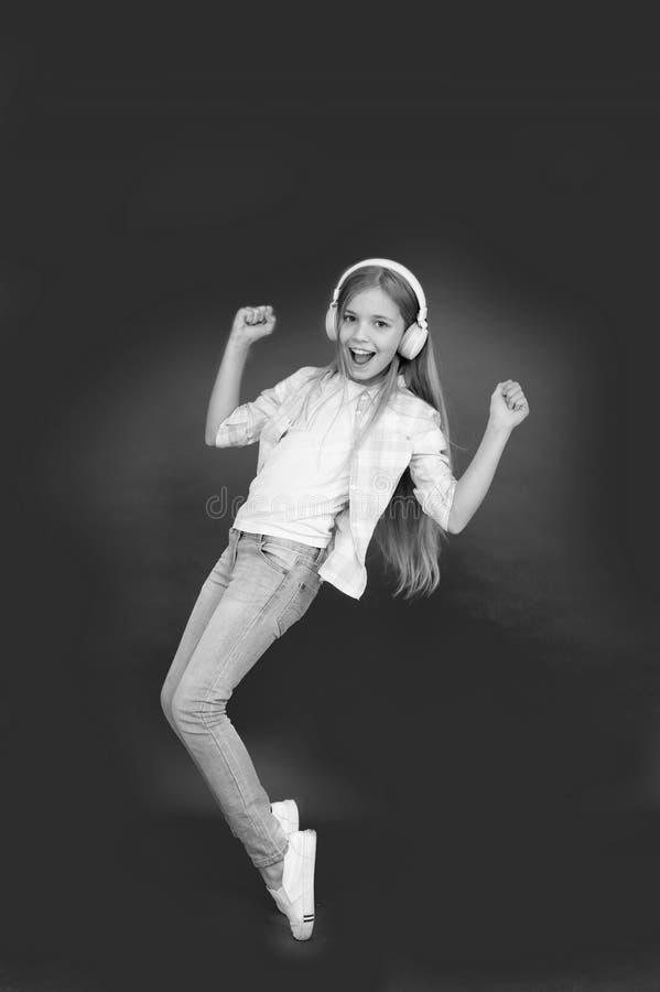 pequeño niño de la muchacha en auriculares Felicidad de la niñez Jugador Mp3 [1] El día de los niños Tecnología audio el pequeño  fotografía de archivo libre de regalías