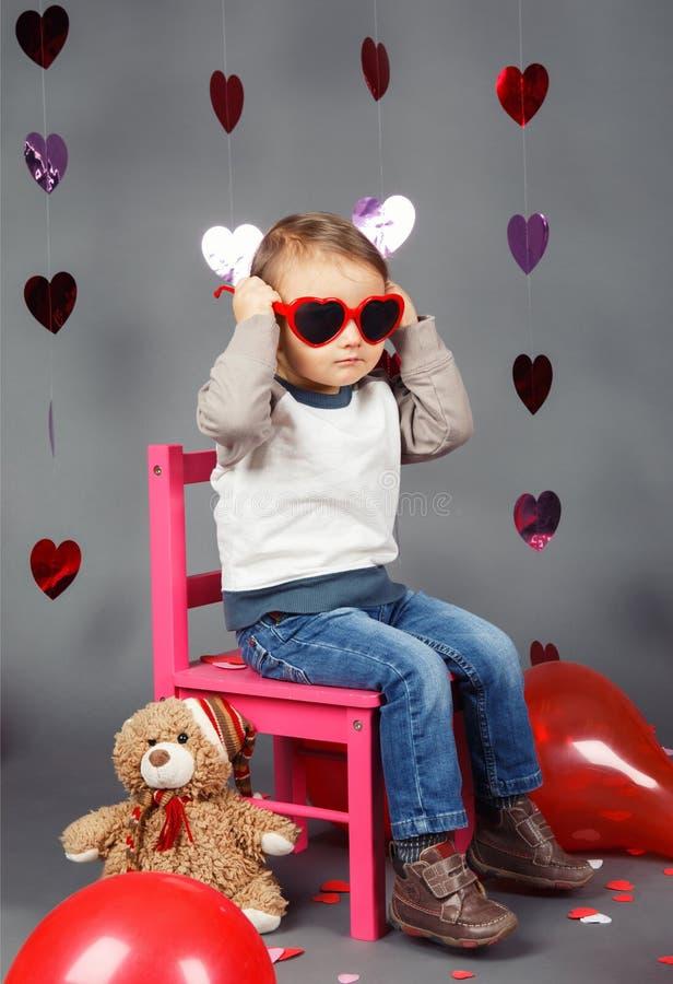 Pequeño niño del bebé que se sienta en pequeña silla rosada con el juguete del oso en el estudio que lleva los vidrios divertidos fotos de archivo libres de regalías
