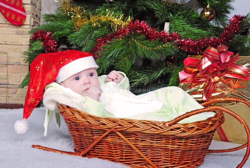 Pequeño niño del pecho en cesta cerca del árbol del abeto del Año Nuevo foto de archivo