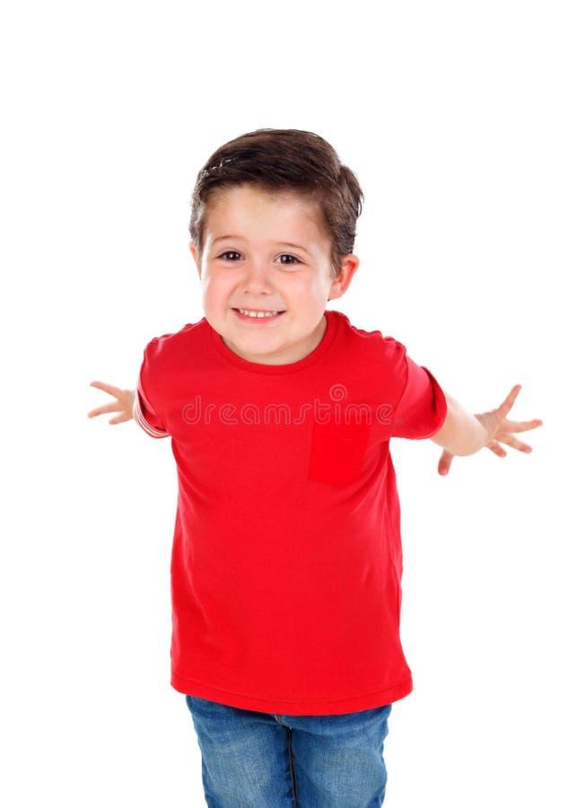 Pequeño niño divertido con el pelo oscuro y los ojos morados que cruzan su brazo fotos de archivo