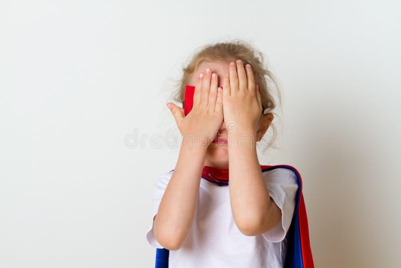 Pequeño niño divertido del superhéroe del poder en un impermeable rojo Concepto del superhéroe fotografía de archivo libre de regalías