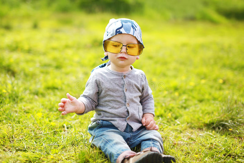 Pequeño niño divertido positivo en gafas de sol imágenes de archivo libres de regalías