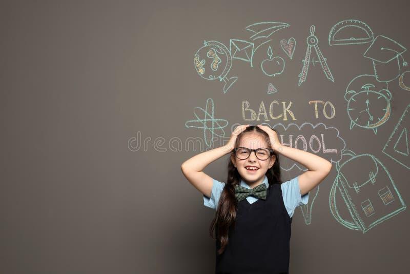 Pequeño niño en dibujos cercanos uniformes con el texto A LA ESCUELA en fondo gris foto de archivo libre de regalías