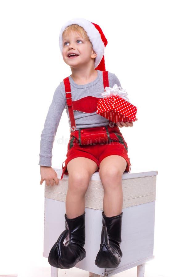 Pequeño niño en traje rojo de la caja de regalo que se sostiene enana con la cinta y la mirada para arriba Navidad foto de archivo libre de regalías