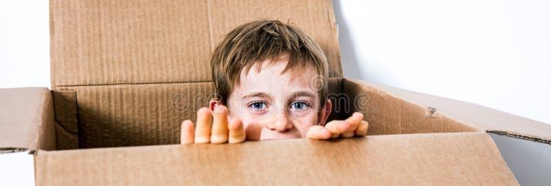 Pequeño niño feliz que oculta en una caja de cartón, jugando peekaboo imagenes de archivo
