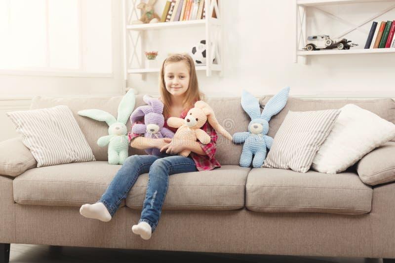 Pequeño niño femenino feliz que abraza sus conejos del juguete en el sofá en casa fotos de archivo