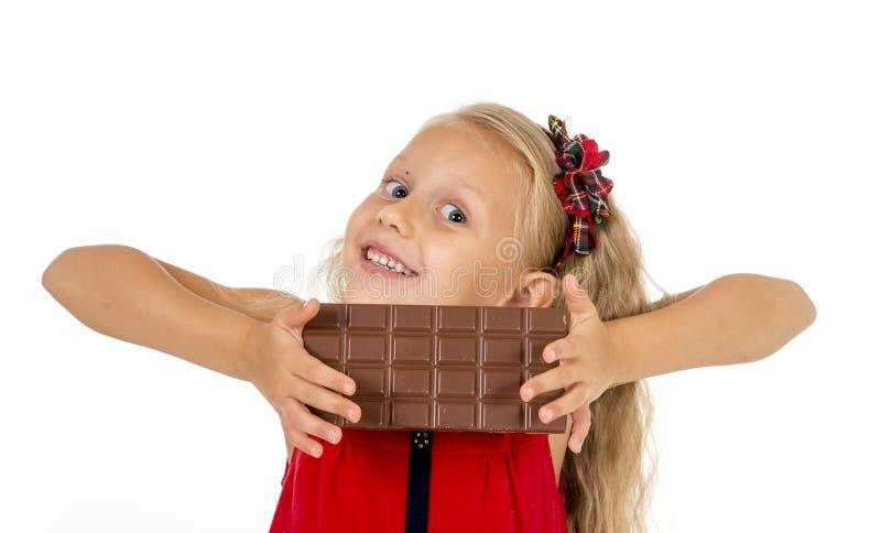 Pequeño niño femenino hermoso en el vestido rojo que sostiene la barra de chocolate deliciosa feliz en su consumición de las mano imágenes de archivo libres de regalías