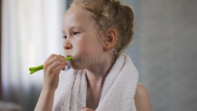 Pequeño niño femenino lindo que cepilla sus dientes, higiene dental, ritual de la mañana fotografía de archivo libre de regalías