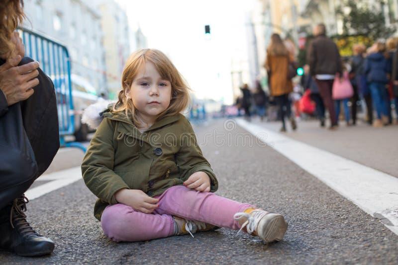 Pequeño niño gritador que se sienta en la calle del asfalto imagenes de archivo
