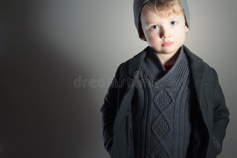 Pequeño niño hermoso de moda de Boy.Stylish. Niños de la moda. en traje, suéter y casquillo imágenes de archivo libres de regalías