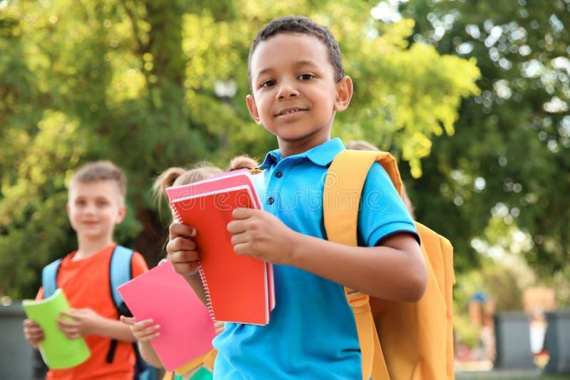 Pequeño niño lindo con la mochila y los cuadernos al aire libre imagen de archivo
