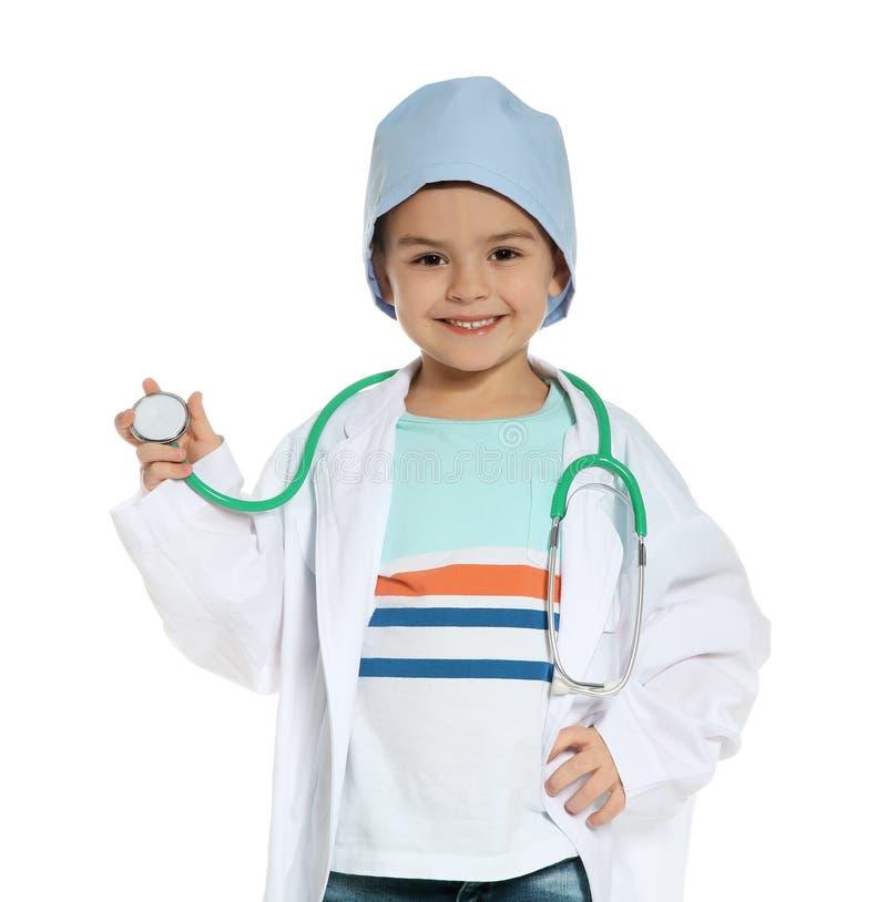 Pequeño niño lindo en capa del doctor con el estetoscopio en blanco imagenes de archivo