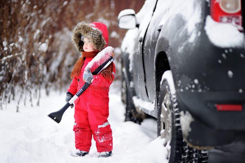 Pequeño niño lindo que ayuda a cepillar una nieve de un coche fotografía de archivo libre de regalías