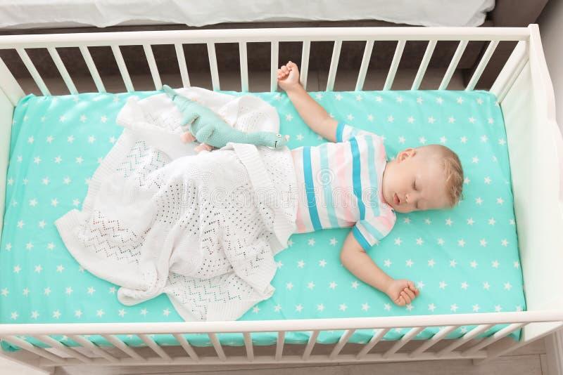 Pequeño niño lindo que duerme en pesebre imágenes de archivo libres de regalías