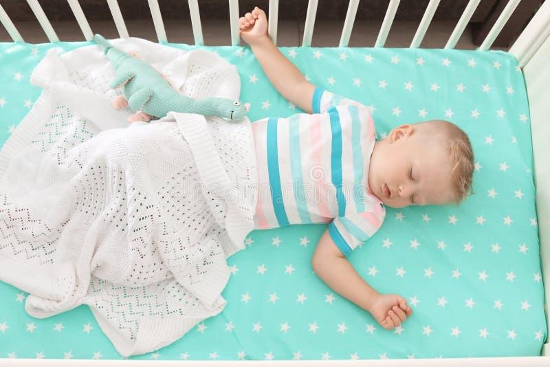 Pequeño niño lindo que duerme en pesebre foto de archivo