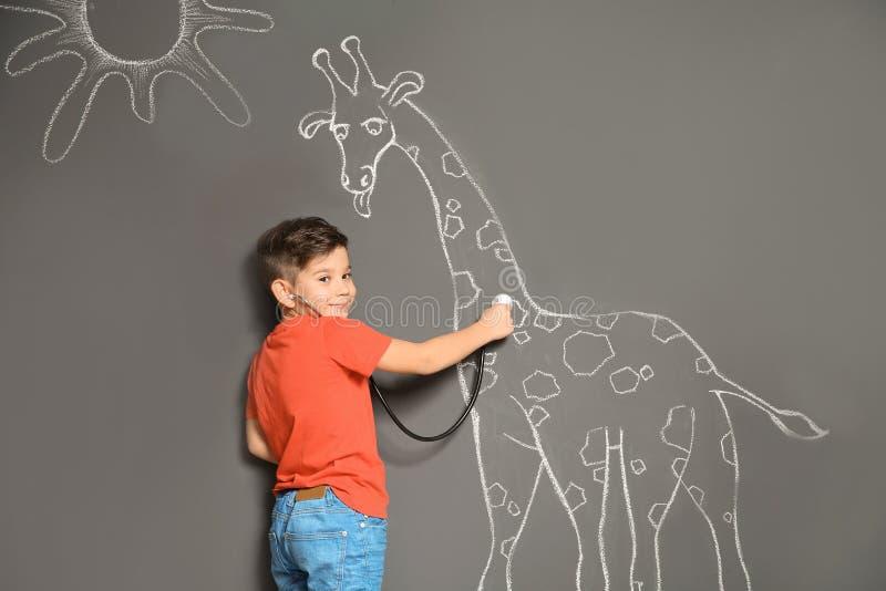 Pequeño niño lindo que juega al doctor con el dibujo de la jirafa de la tiza en gris fotos de archivo libres de regalías