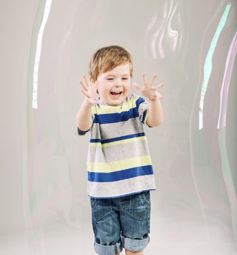 Pequeño niño lindo que juega burbujas de un jabón imagen de archivo