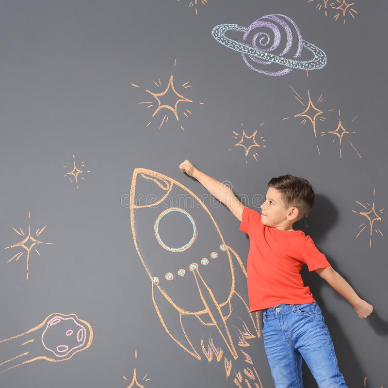 Pequeño niño lindo que juega con el dibujo del cohete de la tiza en gris imágenes de archivo libres de regalías