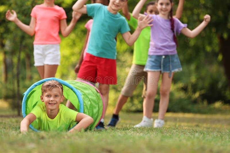 Pequeño niño lindo que juega con los amigos en parque fotografía de archivo