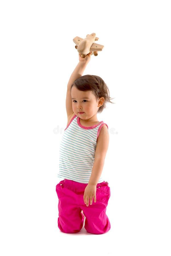 Pequeño niño lindo que juega con un aeroplano del juguete Aislado en blanco imagen de archivo