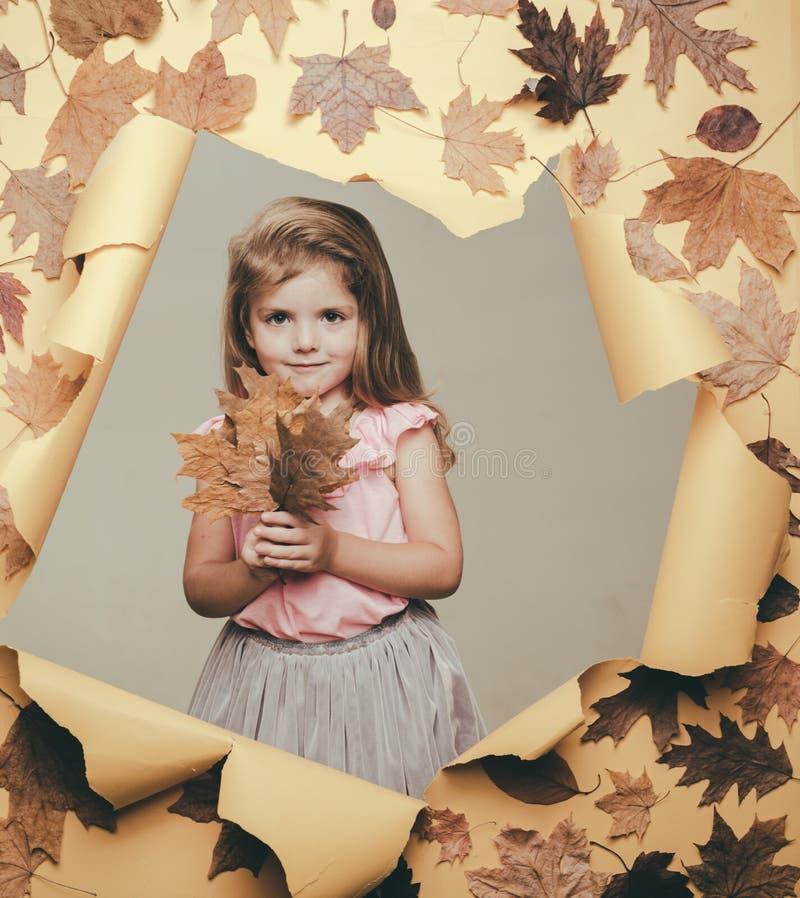 Pequeño niño lindo que sostiene la hoja de oro en fondo amarillo El humor del oto?o y el tiempo son calientes y soleado y lluvia  fotos de archivo