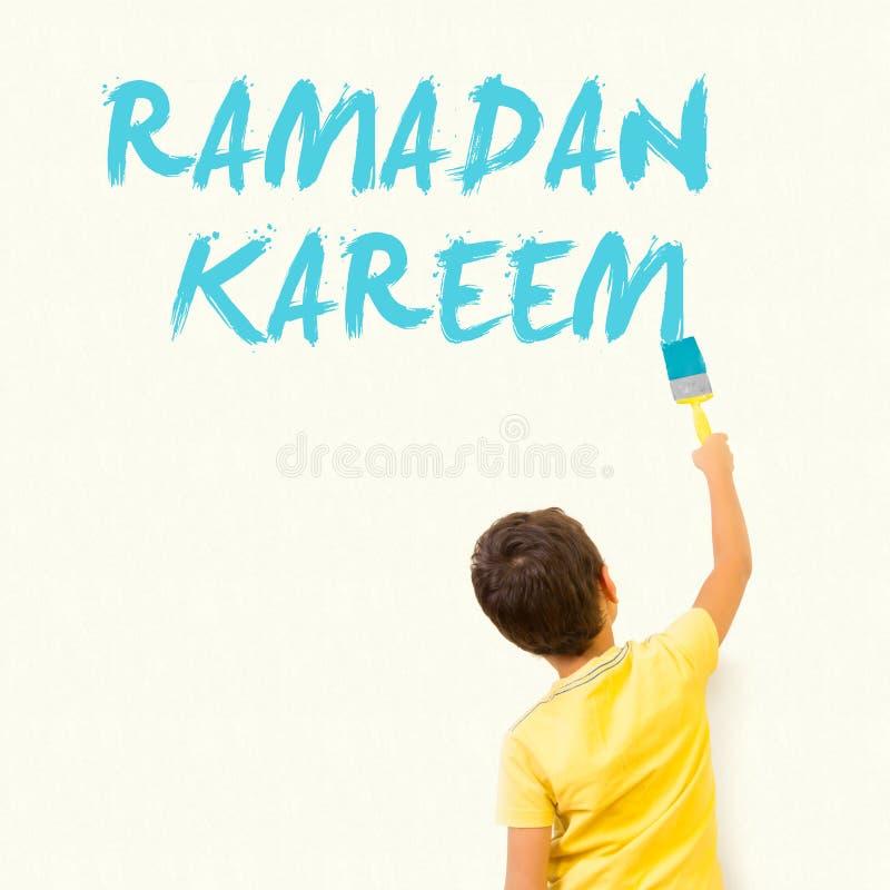 Pequeño niño musulmán lindo que dibuja a Ramadan Kareem