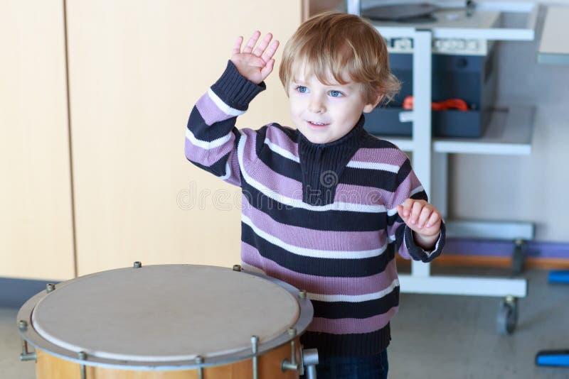 Pequeño niño pequeño que juega el tambor en la escuela de música. foto de archivo