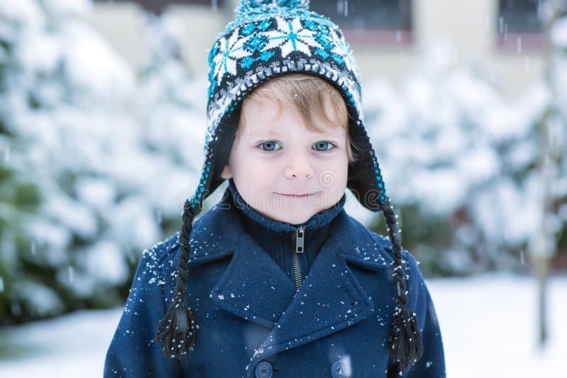 Pequeño niño pequeño que se divierte con nieve al aire libre en los wi hermosos fotos de archivo
