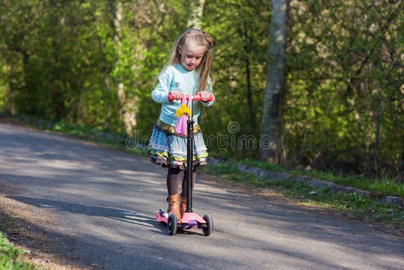 Pequeño niño que aprende montar una vespa en un parque de la ciudad en día de verano soleado juego de los niños al aire libre Oci imagen de archivo