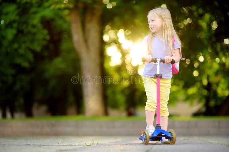 Pequeño niño que aprende montar una vespa en un parque de la ciudad en día de verano soleado Muchacha linda del preescolar en el  fotografía de archivo