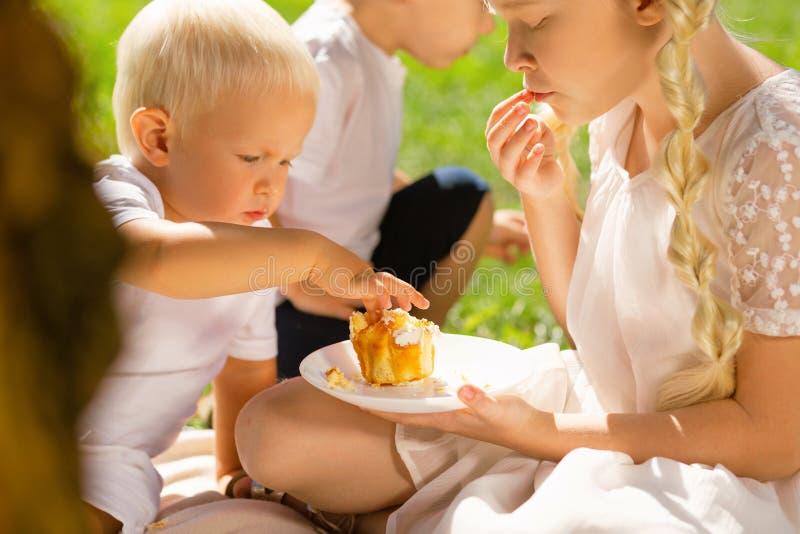 Pequeño niño que come una torta deliciosa en el parque fotografía de archivo