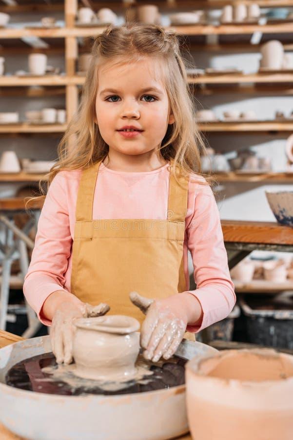 pequeño niño que hace el pote de cerámica con la arcilla en la rueda de la cerámica imágenes de archivo libres de regalías
