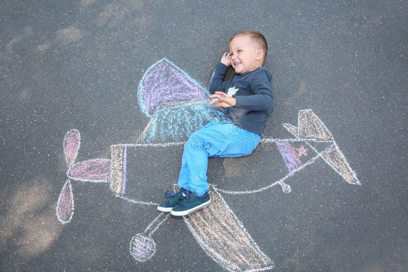 Pequeño niño que miente cerca del dibujo de tiza del aeroplano en el asfalto imagenes de archivo