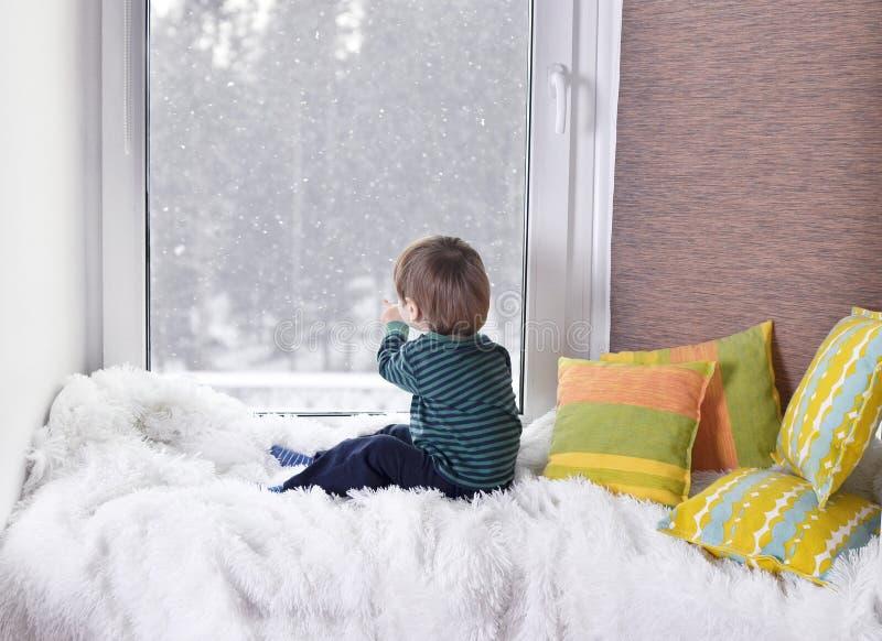 Pequeño niño que mira hacia fuera la ventana imágenes de archivo libres de regalías