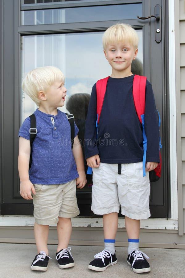 Pequeño niño que mira para arriba a Big Brother en el primer día de escuela fotografía de archivo