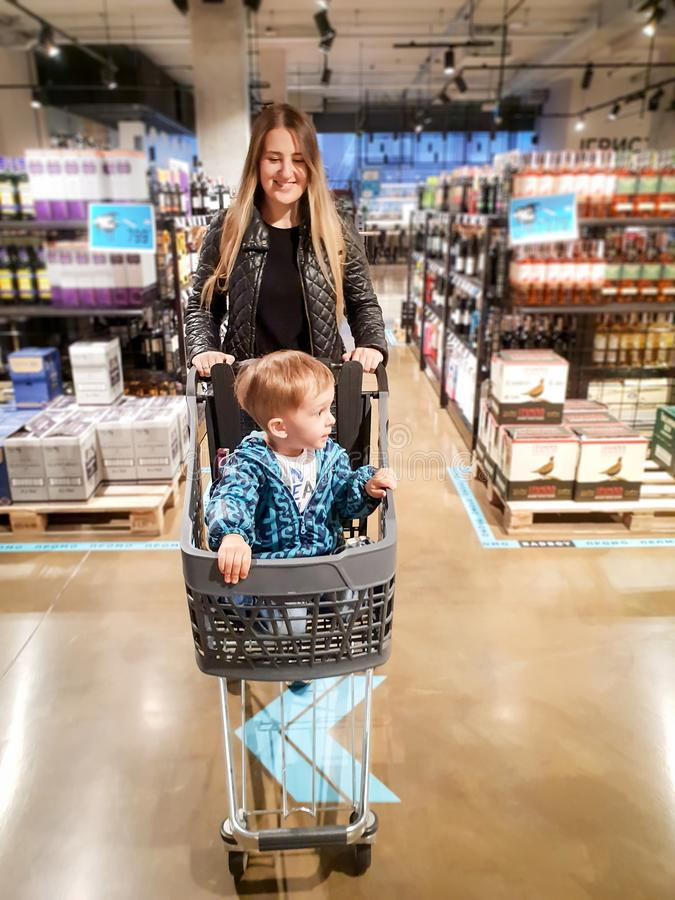 Pequeño niño pequeño que se sienta en carro de la compra mientras que madre que hace compras en tienda fotografía de archivo libre de regalías