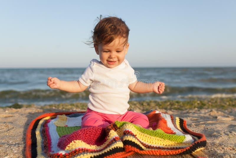 Pequeño niño que se sienta en una manta coloreada en la costa alegre y feliz imágenes de archivo libres de regalías